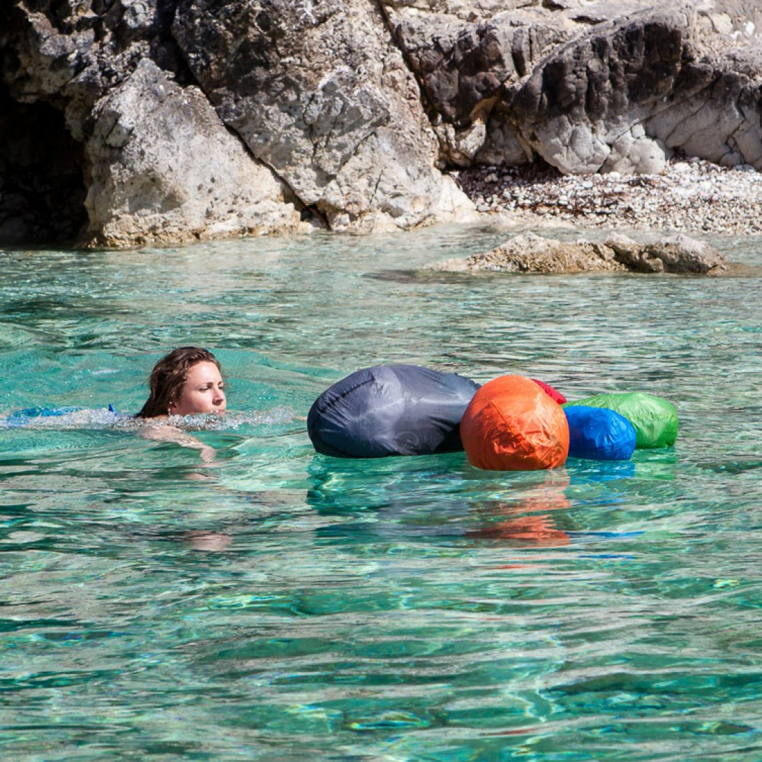 Lady swimming towards roll top dry bags
