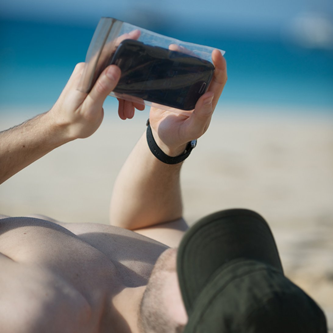 Man laying on beach with phone in waterproof case